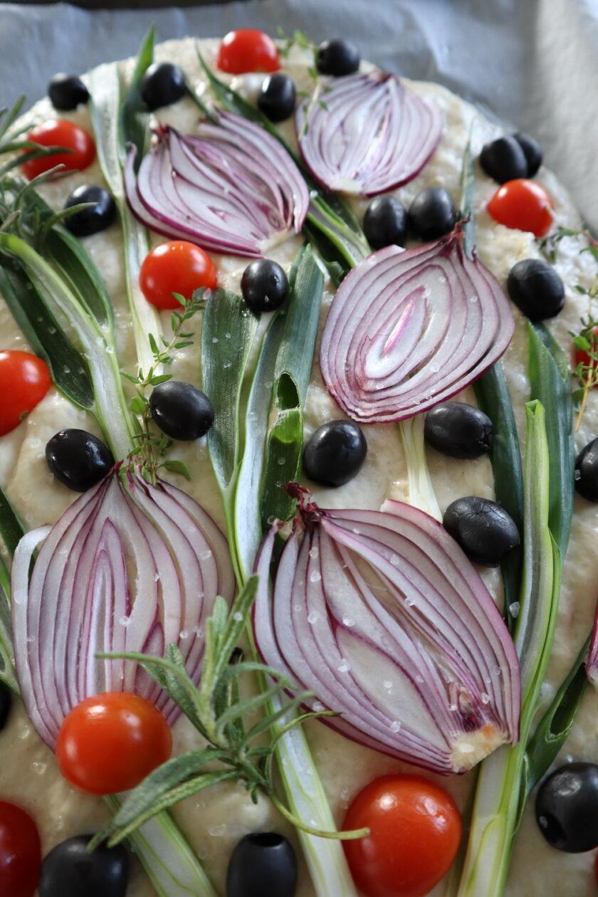Focaccia med rødløg og grønsager før bagning højformat udsnit Bagvrk.dk