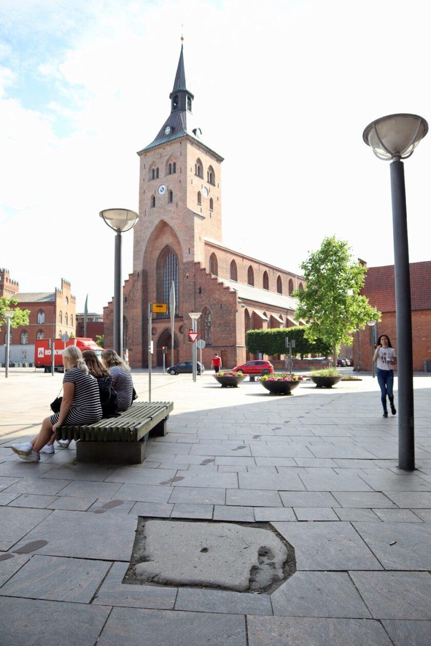 Jomfruspringet hælaftryk i sten foran domkirken Odense Bagvrk.dk
